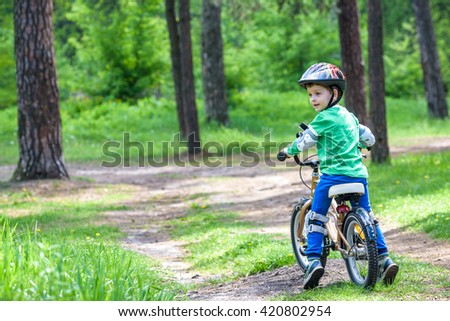 Happy cute blond kid boy having fun his first bike on sunny summer day, outdoors. Happy child making sports. Active leisure for children.