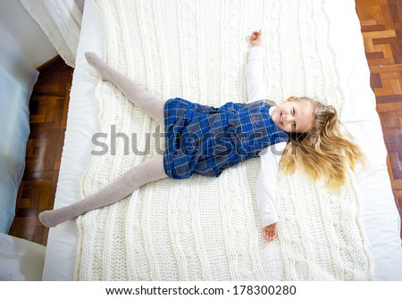 happy cute blonde hair girl smiling at camera lying on the bed shoot from above on a white bed.  - stock photo