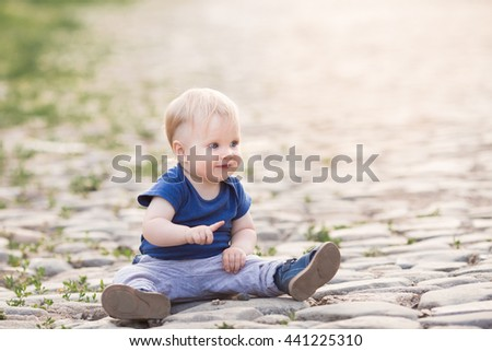 Happy cute boy on old roadway. Smiling one child outdoors on Road paved with stone on the sunset - stock photo