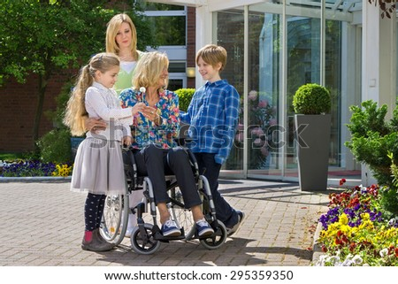 Happy cute caring grandchildren with concerned mother visiting youthful looking grandmother in wheelchair. - stock photo