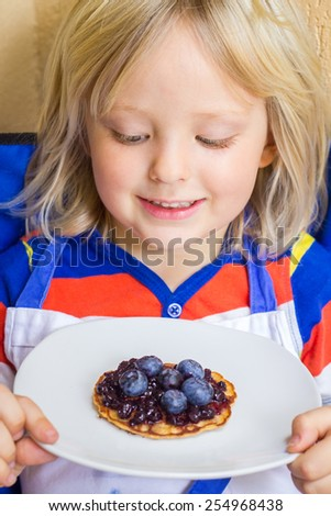 Happy cute child eating homemade healthy snack - stock photo