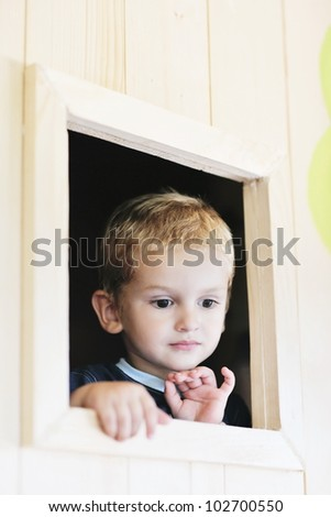 happy cute child in a wooden window at playground