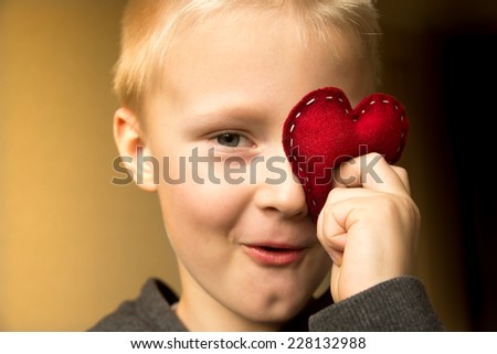 Happy cute child (kid, boy) with hand made red heart. Valentines day and family love concept. Horizontal close up portrait. - stock photo