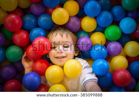 Happy cute child playing and having fun at kindergarten with colorful balls - stock photo