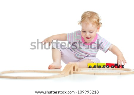 happy cute child playing with toy railroad isolated on white - stock photo