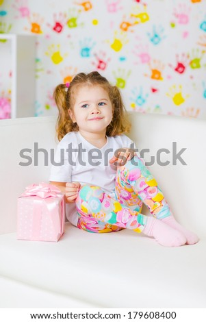 Happy cute child with gift box sitting on sofa  - stock photo