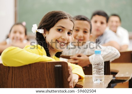 Happy cute children in classroom with their teacher - stock photo
