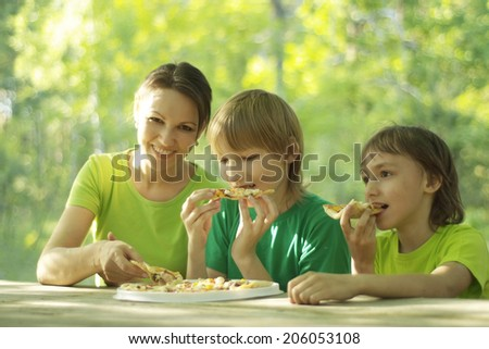 Happy cute family eat pizza together outdoors - stock photo