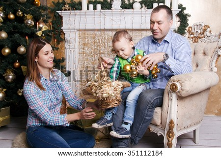 happy cute family sitting near their christmas tree. Mother, Father and their little son enjoy gifts and have a good time together. - stock photo