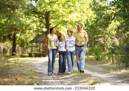Happy cute family walking in summer forest