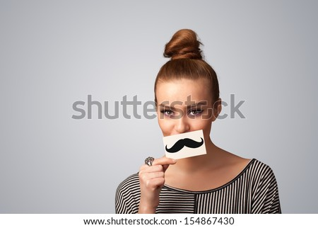 Happy cute girl holding paper with mustache drawing on gradient background - stock photo