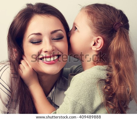 Happy cute kid girl whispering the secret to her laughing mother in ear with fun face. Toned portrait - stock photo