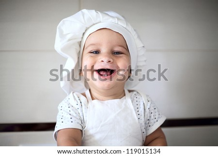 happy cute little baby in a cook cap laughs - stock photo
