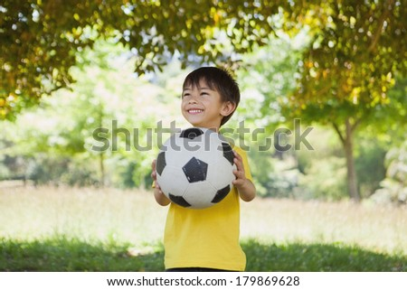 Happy cute little boy with football standing at the park - stock photo
