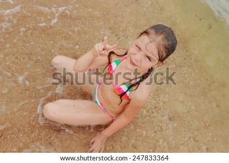 Happy cute little girl in a bright swimsuit play and have fun at the beach on holiday and summer vacation - stock photo
