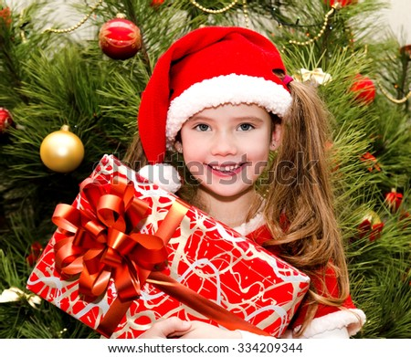 Happy cute little girl in santa hat with gift box near christmas tree - stock photo