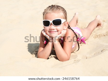 Happy cute little girl in sunglasses lying on the sand on the beach - stock photo