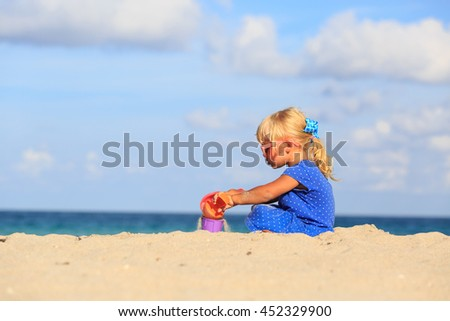 happy cute little girl play with sand on beach