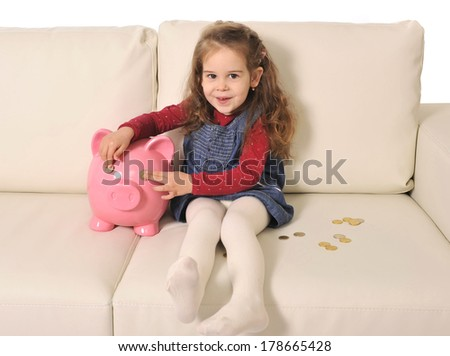Happy Cute little girl playing with coins and huge piggy bank on sofa - stock photo