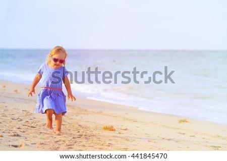 happy cute little girl run on beach - stock photo