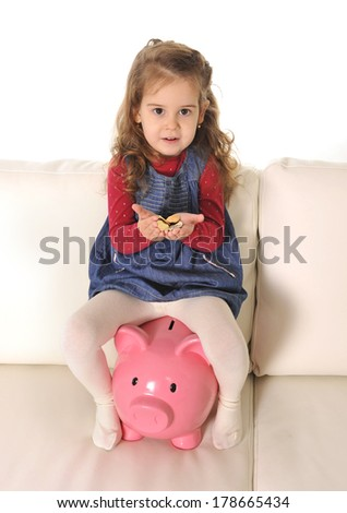 Happy Cute little girl sitting on huge piggy bank holding euro Coins - stock photo