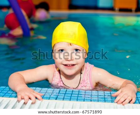 Happy cute little girl wearing yellow swimming cap in a pool - stock photo