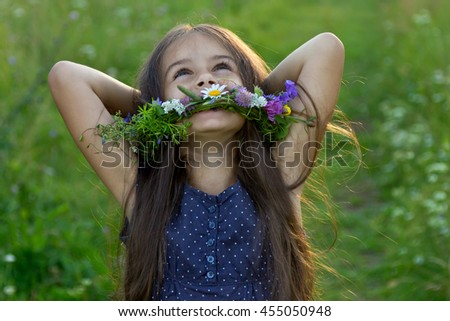 Happy cute little girl with long flowing hair and a wreath of wildflowers laughing with her hands behind head on the summer meadow - stock photo
