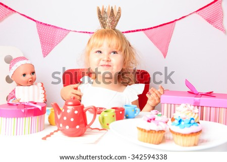 happy cute little girl  with sweets and dolls at birthday party - stock photo