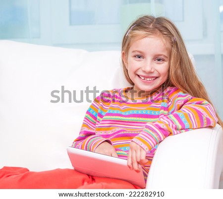 happy cute little girl with the tablet - stock photo