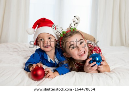 Happy Cute little kid Santa Claus hat and his beautiful sister at Christmas - stock photo