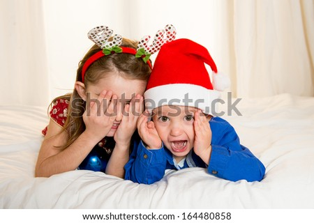 Happy Cute little kid Santa Claus hat and his beautiful sister at Christmas