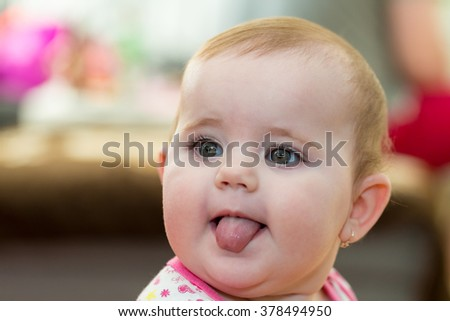 Happy cute little one year old girl indoor smiling and stick your tongue - stock photo