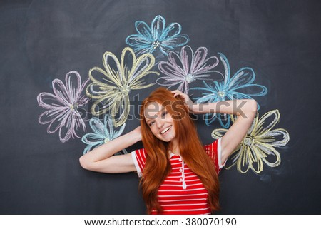 Happy cute lovely young woman standing over chalkboard with drawn colorful flowers  - stock photo