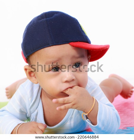 Happy cute 5 month old Asian baby boy with short black hair on rubber floor - stock photo