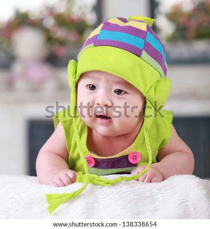 Happy cute 3-month old Chinese baby boy playing on bed with colorful suites - stock photo