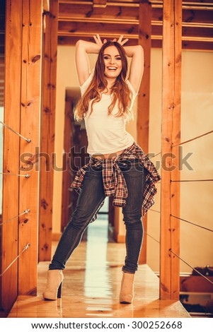 Happy cute pretty gorgeous woman at home showing bunny ears gesture. Attractive young girl with long hair wearing white shirt, jeans trousers and high heels. Instagram filter. - stock photo