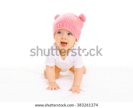 Happy cute smiling baby in knitted pink hat crawls on a white background - stock photo