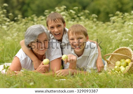 Happy cute smiling family on green summer grass with apples