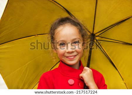 Happy cute smiling girl in a red jacket holding an yellow umbrella in rainy day