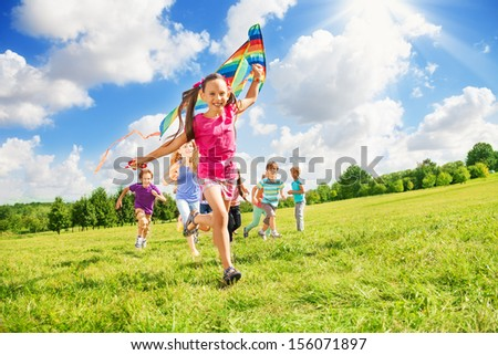 Happy cute smiling girl run with kite and other kids boys and girls running together in the park on sunny day