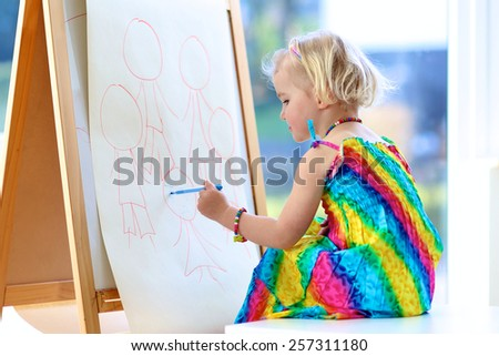 Happy cute toddler girl in colorful dress drawing family on paper using felt pen sitting next to window at home, preschool, daycare or kindergarten enjoying painting art, artistic childhood concept