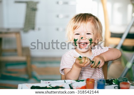 Happy cute toddler painting with gouache paints - stock photo