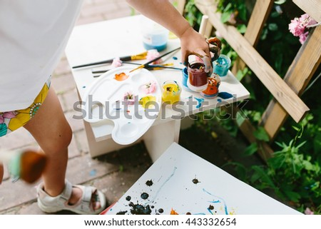 Happy cute toddler painting with gouache paints outdoors in the garden - stock photo