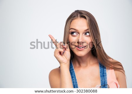 Happy cute woman pointing finger away isolated on a white background - stock photo