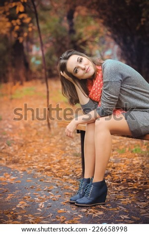 Happy cute woman sitting on a bench in evening park. - stock photo