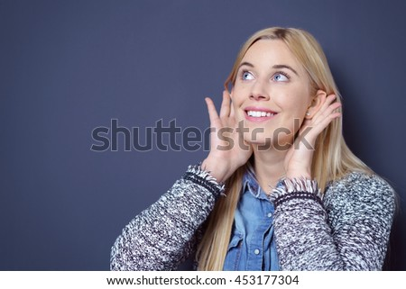 Happy cute young blond lady in sweater and blue buttoned shirt holding both hands to ears while looking upwards as if to listen to something over dark background with copy space - stock photo