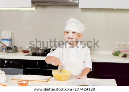 Happy cute young boy baking in the kitchen in a chefs uniform grinning from ear to ear as he displays a face full of flour - stock photo