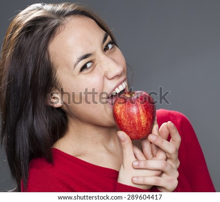 happy cute young brunette with red sweater biting red apple with good appetite