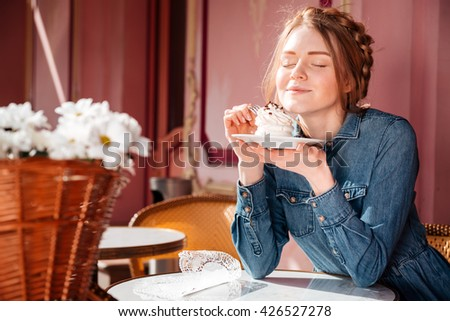 Happy cute young woman eating sweet tasty cupcake in outdoor cafe - stock photo