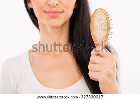 Happy cute young woman holding hairbrush